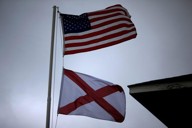 A U.S. flag and an Alabama State flag wave in the wind in Dauphin Island, Alabama, U.S., September 5, 2018. REUTERS/Jonathan Bachman