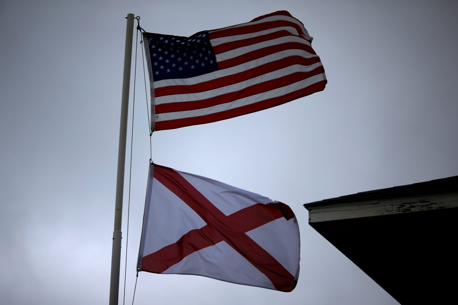 A U.S. flag and an Alabama State flag wave in the wind in Dauphin Island, Alabama, U.S., September 5, 2018. REUTERS/Jonathan Bachman