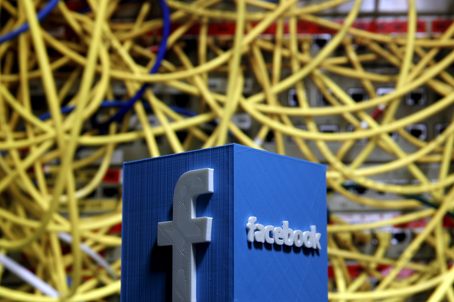 FILE PHOTO: A 3D plastic representation of the Facebook logo is seen in front of displayed cables in this illustration in Zenica, Bosnia and Herzegovina May 13, 2015. REUTERS/Dado Ruvic/File Photo