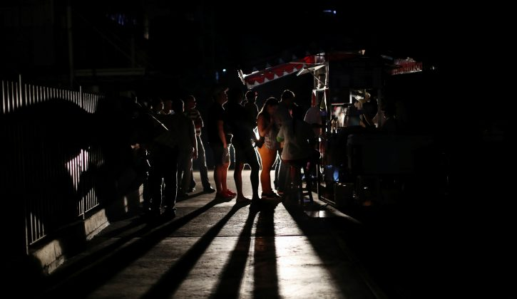 Locals gather at a street food cart during a blackout in Caracas, March 29. REUTERS/Ivan Alvarado