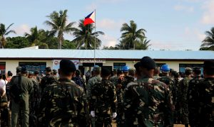 FILE PHOTO - A Philippine flag flutters in Philippine occupied (Pagasa) Thitu island, in disputed South China Sea, as soldiers and civilians sing the country's national anthem April 21, 2017. REUTERS/Erik De Castro