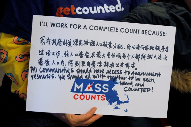 FILE PHOTO: A community activist holds a sign in Chinese and English at an event to mark the one-year-out launch of the 2020 Census efforts in Boston, Massachusetts, U.S., April 1, 2019. REUTERS/Brian Snyder/File Photo