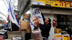 A man holds a Likud election campaign poster depicting Israeli Prime Minister Benjamin Netanyahu as he stands behind a stall at Mahane Yehuda Market in Jerusalem April 8, 2019. REUTERS/Ronen Zvulun