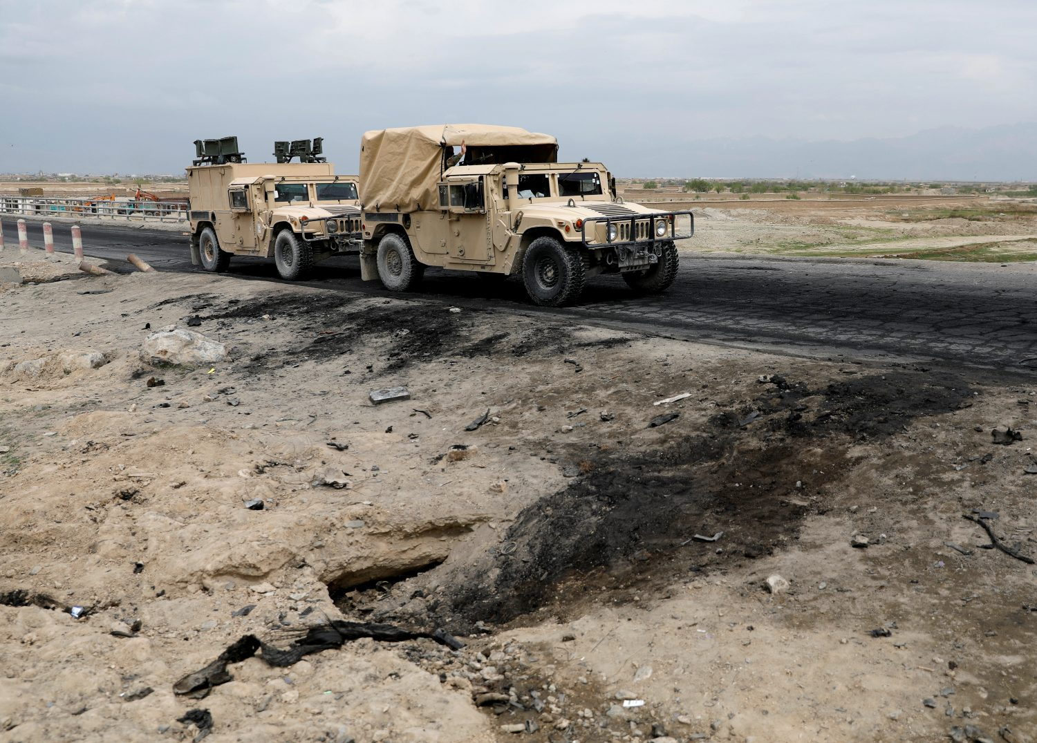 An Afghan military convoy drives past the site of a car bomb attack where U.S soldiers were killed near Bagram air base, Afghanistan April 9, 2019. REUTERS/Mohammad Ismail