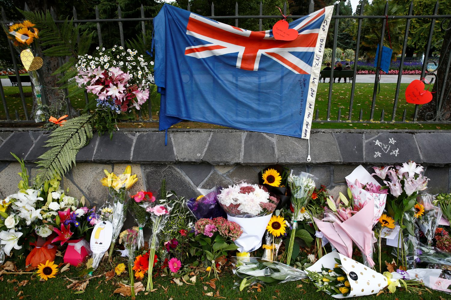Flowers and a New Zealand national flag are seen at a memorial as tributes to victims of the mosque attacks near Linwood mosque in Christchurch, New Zealand, March 16, 2019. REUTERS/Edgar Su