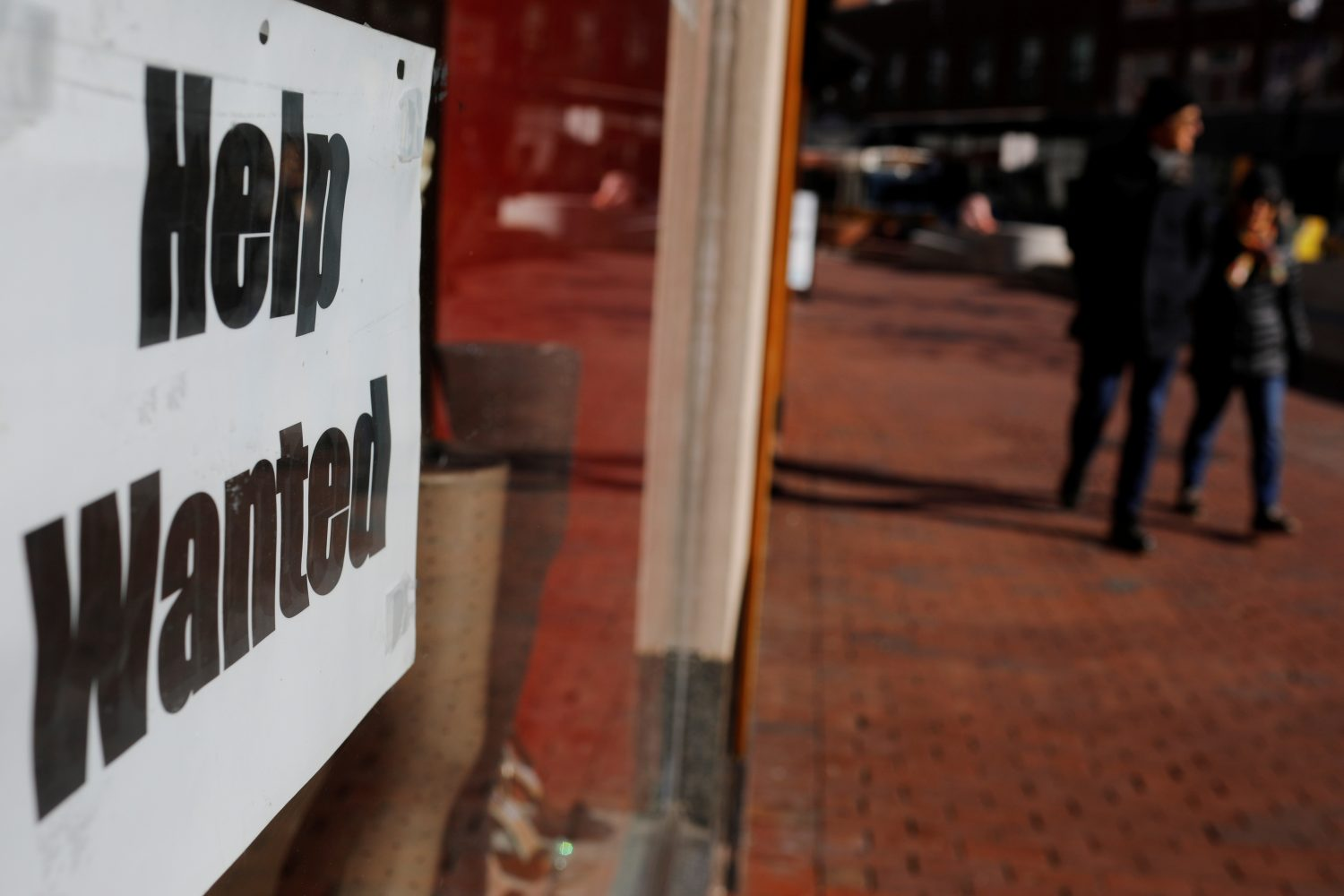 """FILE PHOTO: A """"Help Wanted"""" sign sits in the window of a shop in Harvard Square in Cambridge, Massachusetts, U.S., February 11, 2019. REUTERS/Brian Snyder/File Photo"""