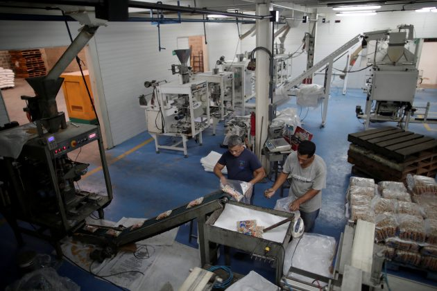Men work on the only operative production line at a food packaging plant in Valencia, Venezuela, April 8, 2019. Picture taken April 8, 2019. REUTERS/Ueslei Marcelino