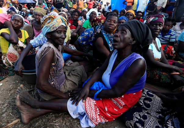 FILE PHOTO: Women wait to receive aid at a camp for the people displaced in the aftermath of Cyclone Idai in John Segredo near Beira, Mozambique March 31, 2019. REUTERS/Zohra Bensemra