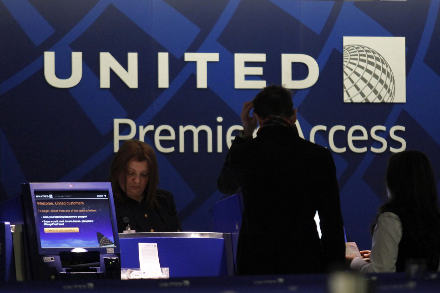 FILE PHOTO: A worker from United attends to some customers during their check in process at Newark International airport in New Jersey , November 15, 2012. REUTERS/Eduardo Munoz/File Photo