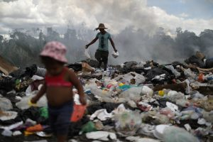 Venezuelan Antony Calzadilla is seen at a garbage dump as his child waits for him, in the border city of Pacaraima, Brazil April 13, 2019. Picture taken April 13, 2019. REUTERS/Pilar Olivares