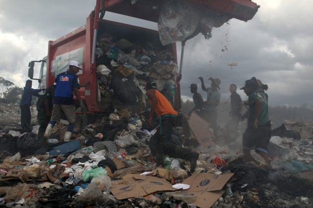 Venezuelan migrants wait while the rubbish truck unload at the garbage dump in the border city of Pacaraima, Brazil April 13, 2019. Picture taken April 13, 2019. REUTERS/Pilar Olivares