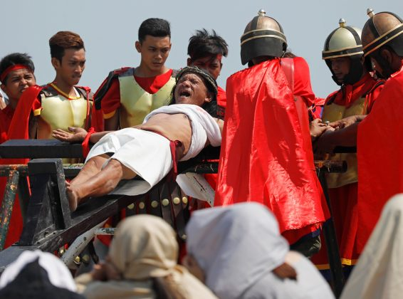 Ruben Enaje, 58, who portrays Jesus Christ, grimaces in pain after being nailed on a wooden cross during crucifixion re-enactment on Good Friday, in San Fernando City, Pampanga province, Philippines, April 19, 2019. REUTERS/Eloisa Lopez