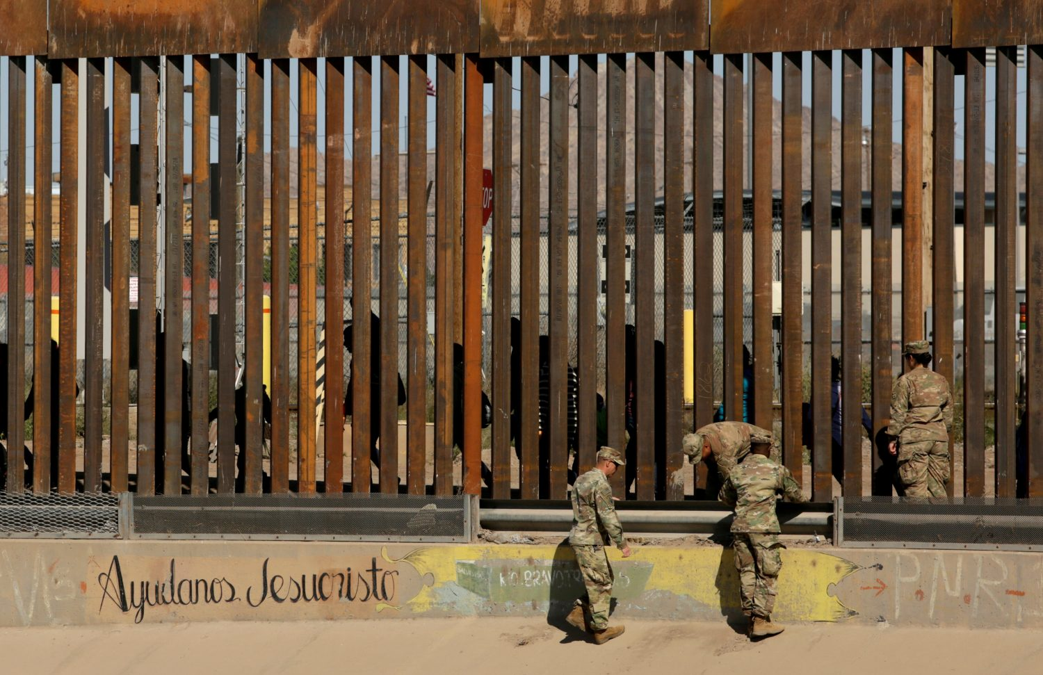 "FILE PHOTO: U.S. soldiers walk next to the border fence between Mexico and the United States, as migrants are seen walking behind the fence, after crossing illegally into the U.S. to turn themselves in, in El Paso, Texas, U.S., in this picture taken from Ciudad Juarez, Mexico, April 3, 2019. The writing on the wall reads, ""Help us Jesus Christ."" REUTERS/Jose Luis Gonzalez/File Photo"