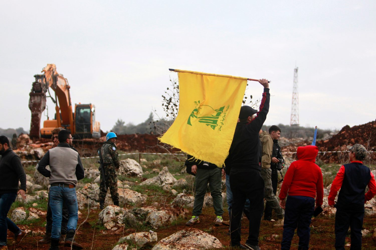 FILE PHOTO: A man holds a Hezbollah flag at Meis al-Jabal village in south Lebanon, December 9, 2018. REUTERS/Aziz Taher