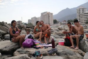 "Leonel Martinez, who works as soldier, kisses his girlfriend as they spend a day at Coral beach in La Guaira near Caracas, Venezuela, March 23, 2019. ""It's a way to think about something besides what is happening in the country,"" said Martinez. ""It's not something you can do every day, because of the situation in the country."" REUTERS/Ivan Alvarado"