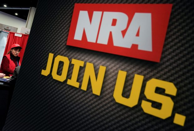An attendee speaks to representatives of the National Rifle Association (NRA) at the Conservative Political Action Conference (CPAC) annual meeting at National Harbor in Oxon Hill, Maryland