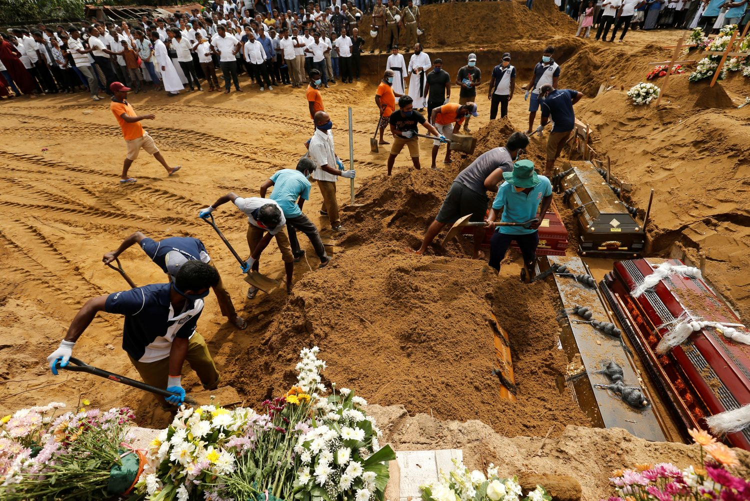 Coffins are laid in the ground during a mass burial for victims at a cemetery near St Sebastian's Church in Negombo, three days after a string of suicide bomb attacks on churches and luxury hotels across the island on Easter Sunday, in Sri Lanka April 24, 2019. REUTERS/Thomas Peter