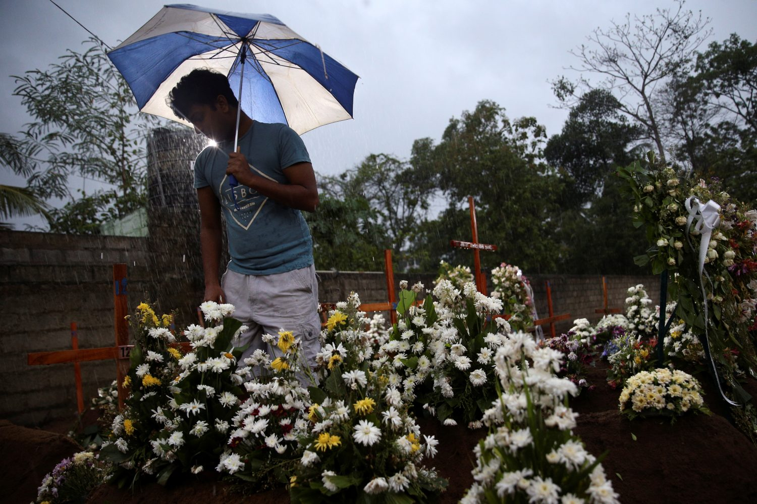 A man comes to the site of a mass burial to pay his respects to victims of a string of suicide bomb attacks on churches and luxury hotels on Easter Sunday, in Negombo, Sri Lanka April 25, 2019. REUTERS/Athit Perawongmetha