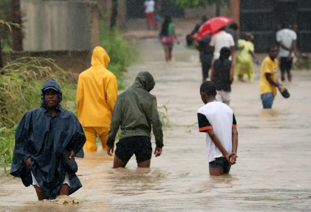 Residents wade through a flooded road in the aftermath of Cyclone Kenneth in Pemba, Mozambique, April 28, 2019. REUTERS/Mike Hutchings