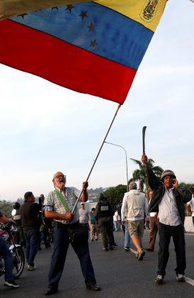 "An opposition supporter waves a Venezuelan flag near the Generalisimo Francisco de Miranda Airbase ""La Carlota"", in Caracas, Venezuela April 30, 2019. REUTERS/Carlos Garcia Rawlins"