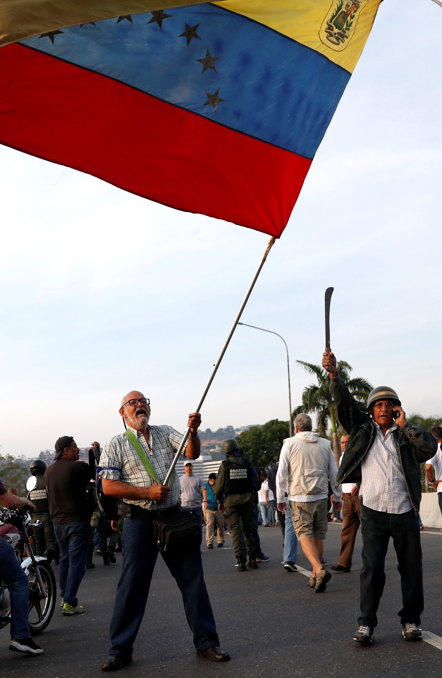 "An opposition supporter waves a Venezuelan flag near the Generalisimo Francisco de Miranda Airbase ""La Carlota"", in Caracas, Venezuela April 30, 2019. REUTERS/Carlos Garcia Rawlins"