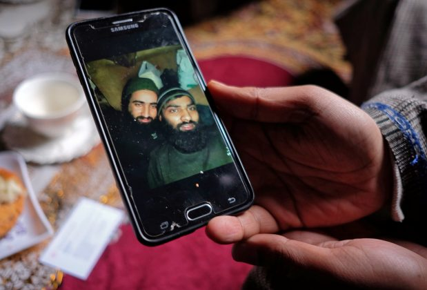 Bilal Ahmad Naikoo, a civilian, displays a photo of his brother Hilal with Rashid Bhai, a Pakistani national, both members of Pakistan-based militant group Jaish-e-Mohammed (JeM), who were killed in a gun battle with Indian army in Pinglan village in south Kashmir's Pulwama district March 21, 2019. REUTERS/Stringer