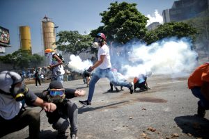 "Opposition demonstrators take cover from tear gas on a street near the Generalisimo Francisco de Miranda Airbase ""La Carlota"" in Caracas, Venezuela April 30, 2019. REUTERS/Ueslei Marcelino"