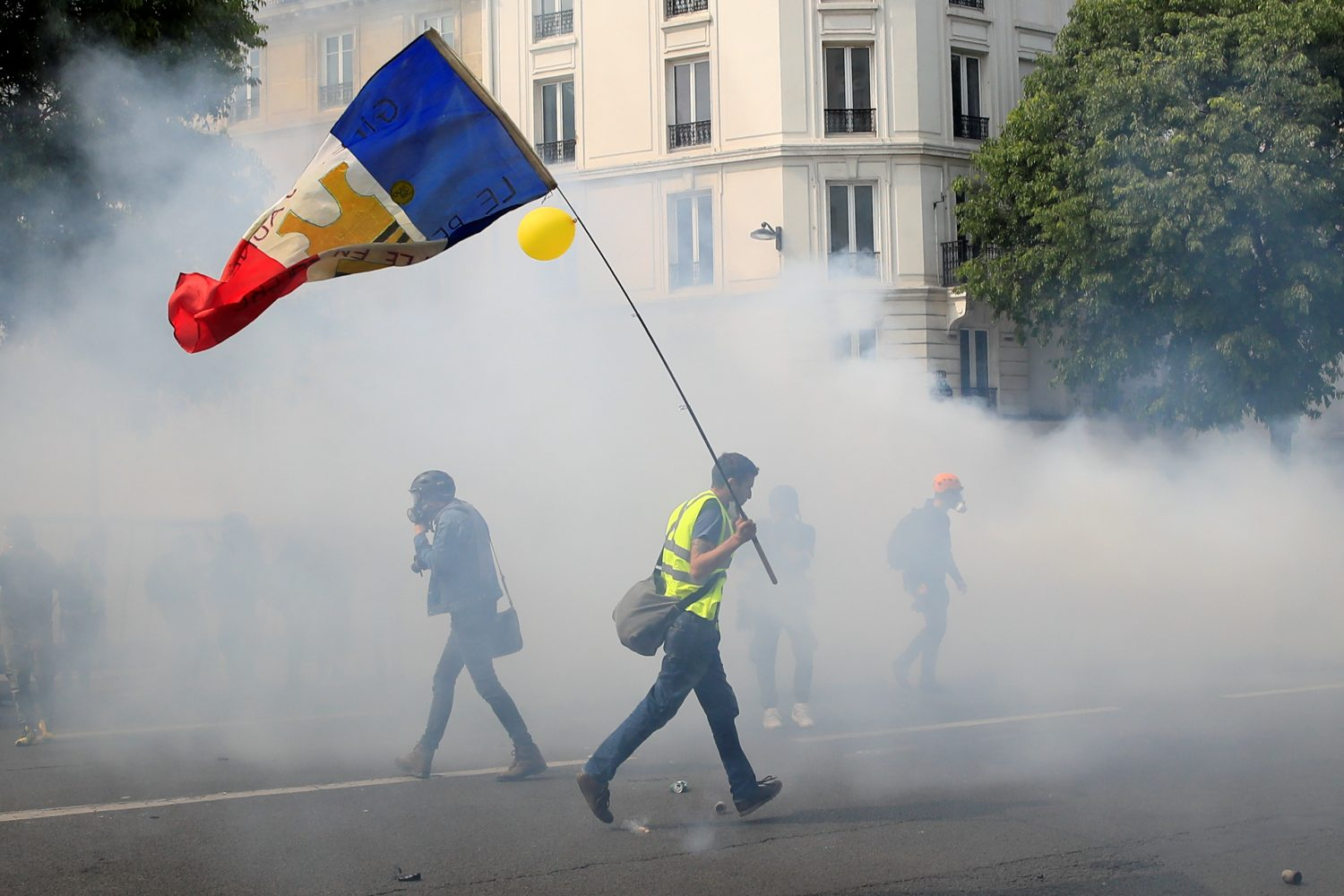 A protester wearing a yellow vest holds a French flag as he walks among tear gas during the traditional May Day labour union march with French unions and yellow vests protesters in Paris, France, May 1, 2019. REUTERS/Gonzalo Fuentes
