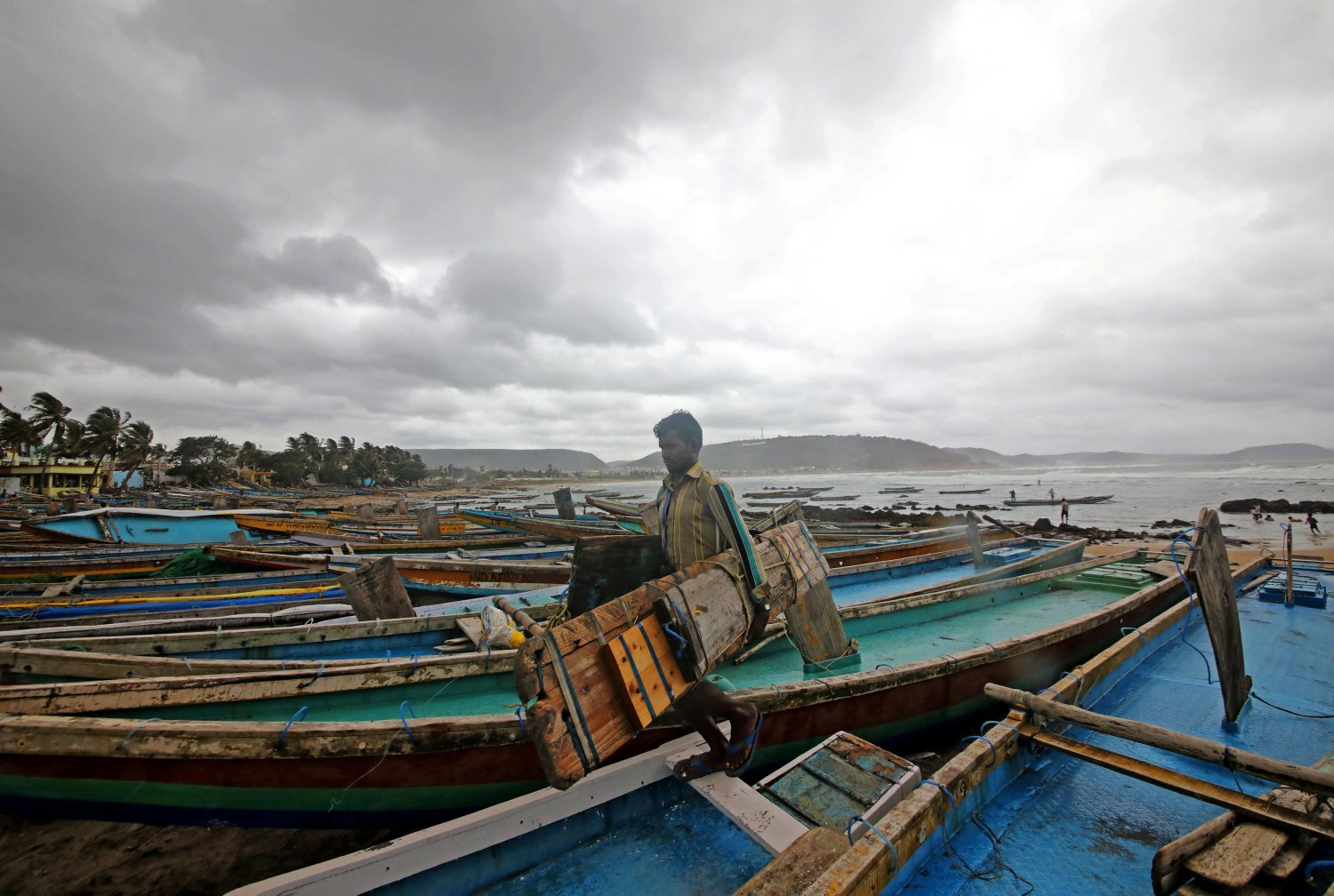 A fisherman carries his tools as he leaves for a safer place after tying his boats along the shore ahead of cyclone Fani in Peda Jalaripeta on the outskirts of Visakhapatnam, India, May 1, 2019. REUTERS/Stringer