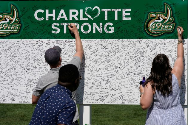 FILE PHOTO: Patrons sign a board to show their sentiments in support of UNC Charlotte after the recent shooting deaths during the second round of the Wells Fargo Championship golf tournament at the Quail Hollow Club in Charlotte, North Carolina, U.S., May 3, 2019. Mandatory Credit: Jim Dedmon-USA TODAY Sports/File Photo
