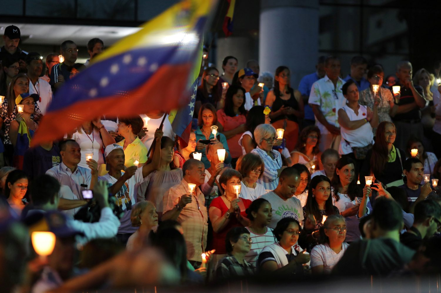 People hold lit candles and Venezuelan flags while participating in a candlelight vigil held for victims of recent violence in Caracas, Venezuela May 5, 2019. REUTERS/Manaure Quintero