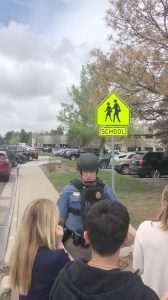 A police officer reassures people waiting outside near the STEM School during a shooting incident in Highlands Ranch, Colorado, U.S. in this May 7, 2019 still frame obtained via social media video. SHREYA NALLAPATI/VIA REUTERS