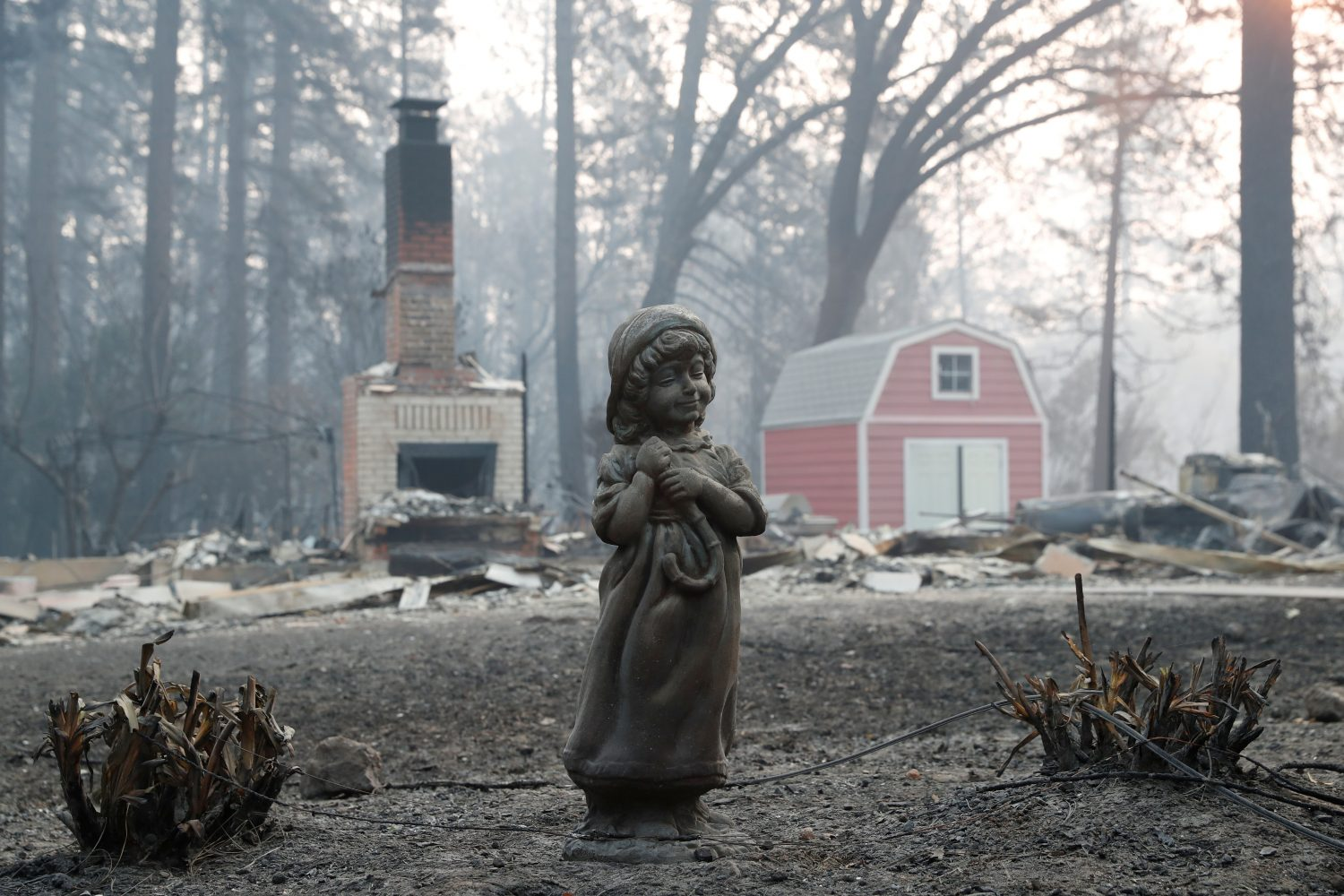 FILE PHOTO: A statue stands in front of a home destroyed by the Camp Fire in Paradise, California, U.S., November 17, 2018. REUTERS/Terray Sylvester/File Photo