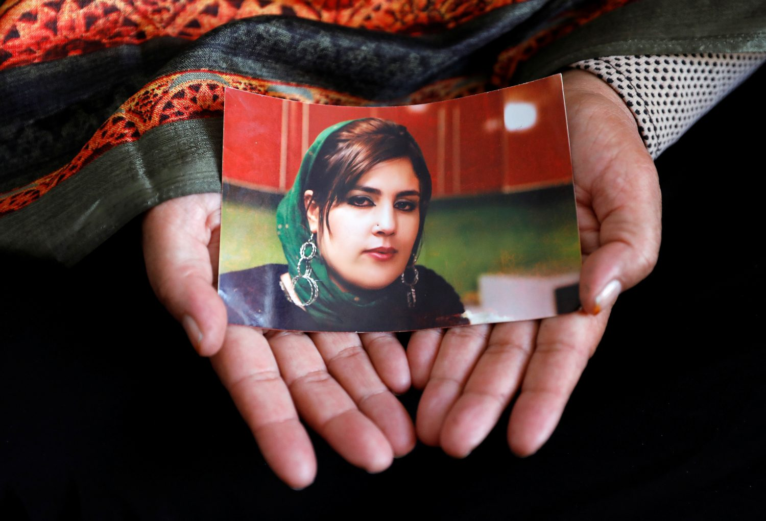 Anisa Mangal holds a photo of her daughter Mena Mangal, an Afghan journalist and parliamentary adviser, who was recently killed in Kabul, Afghanistan May 14, 2019. Picture taken May 14, 2019. REUTERS/Mohammad Ismail