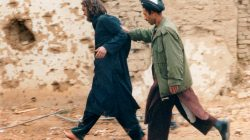 FILE PHOTO: U.S.-born John Walker Lindh (L) is led away by a Northern Alliance soldier after he was captured among al Qaeda and Taliban prisoners following an uprising at the Fort Qali-i-Janghi prison near Mazar-i-Sharif December 1, 2001 REUTERS/STR/File Photo