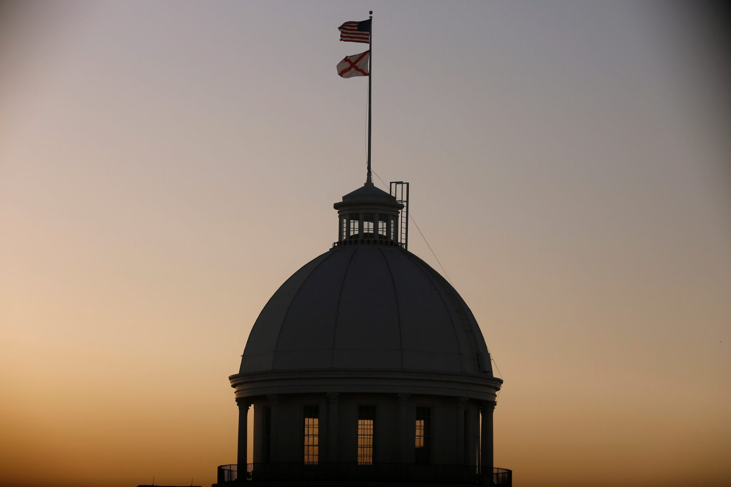 FILE PHOTO: The U.S. Flag and Alabama State Flag fly over the Alabama Governor's Mansion as the state Senate votes on the strictest anti-abortion bill in the United States at the Alabama Legislature in Montgomery, Alabama, U.S. May 14, 2019. REUTERS/Chris Aluka Berry