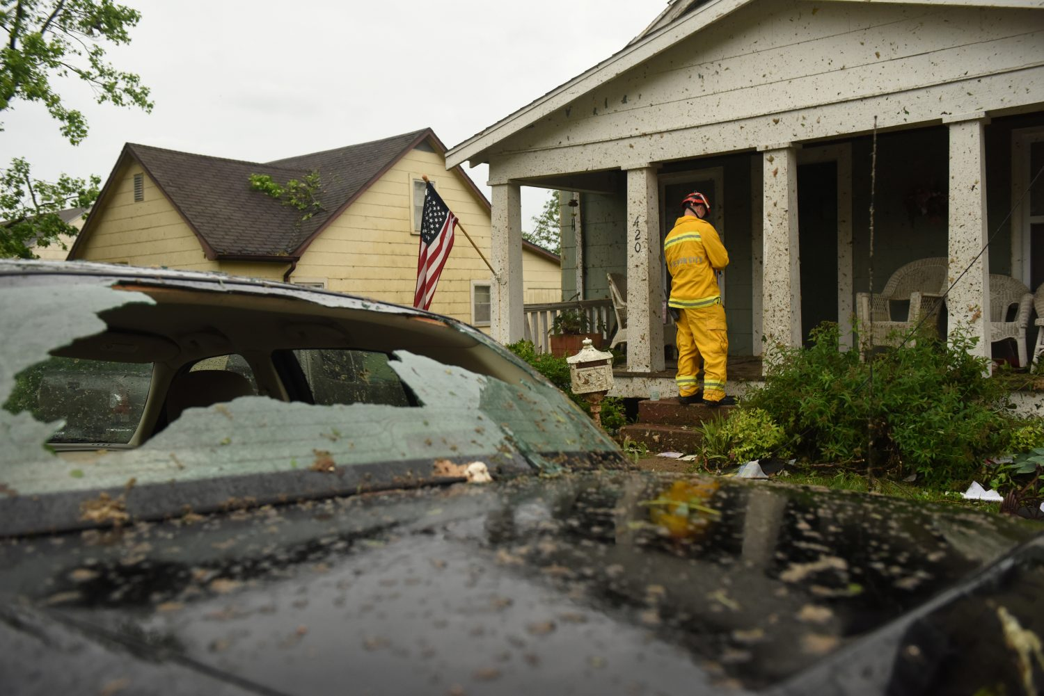 A member of the Jefferson City Fire Department checks houses for people on Woodland Avenue following a tornado touchdown overnight in Jefferson City, Missouri, U.S. May 23, 2019. REUTERS/Antranik Tavitian