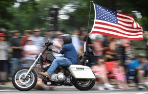 "A motorcycle rider with American flag fluttering passes crowds during the 32nd Annual, and possibly final, Rolling Thunder ""Ride for Freedom"" during Memorial Day weekend to support veterans and call attention to POWs and MIAs, in Washington, U.S., May 26, 2019.REUTERS/Mike Theiler"