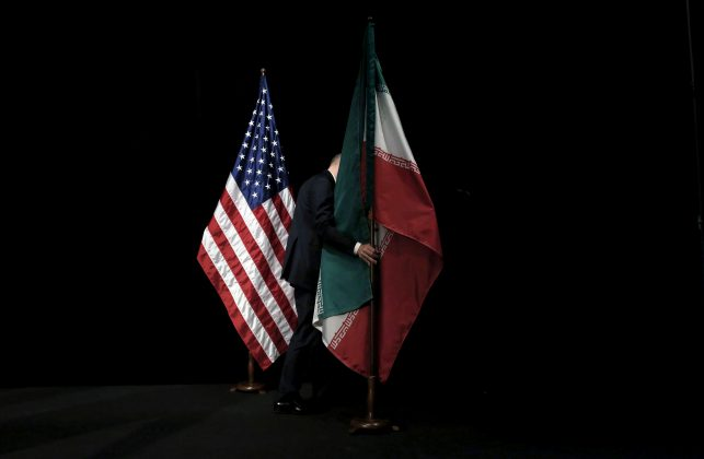FILE PHOTO: A staff member removes the Iranian flag from the stage after a group picture with foreign ministers and representatives of the U.S., Iran, China, Russia, Britain, Germany, France and the European Union during Iran nuclear talks at the Vienna International Center in Vienna, Austria, July 14, 2015. REUTERS/Carlos Barria/File Photo