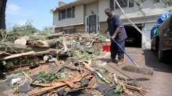 A man named Luther cleans up his driveway of debris after a tornado touched down overnight in city of Trotwood near Dayton, Ohio, U.S. May 28, 2019. REUTERS/Aaron Josefczyk