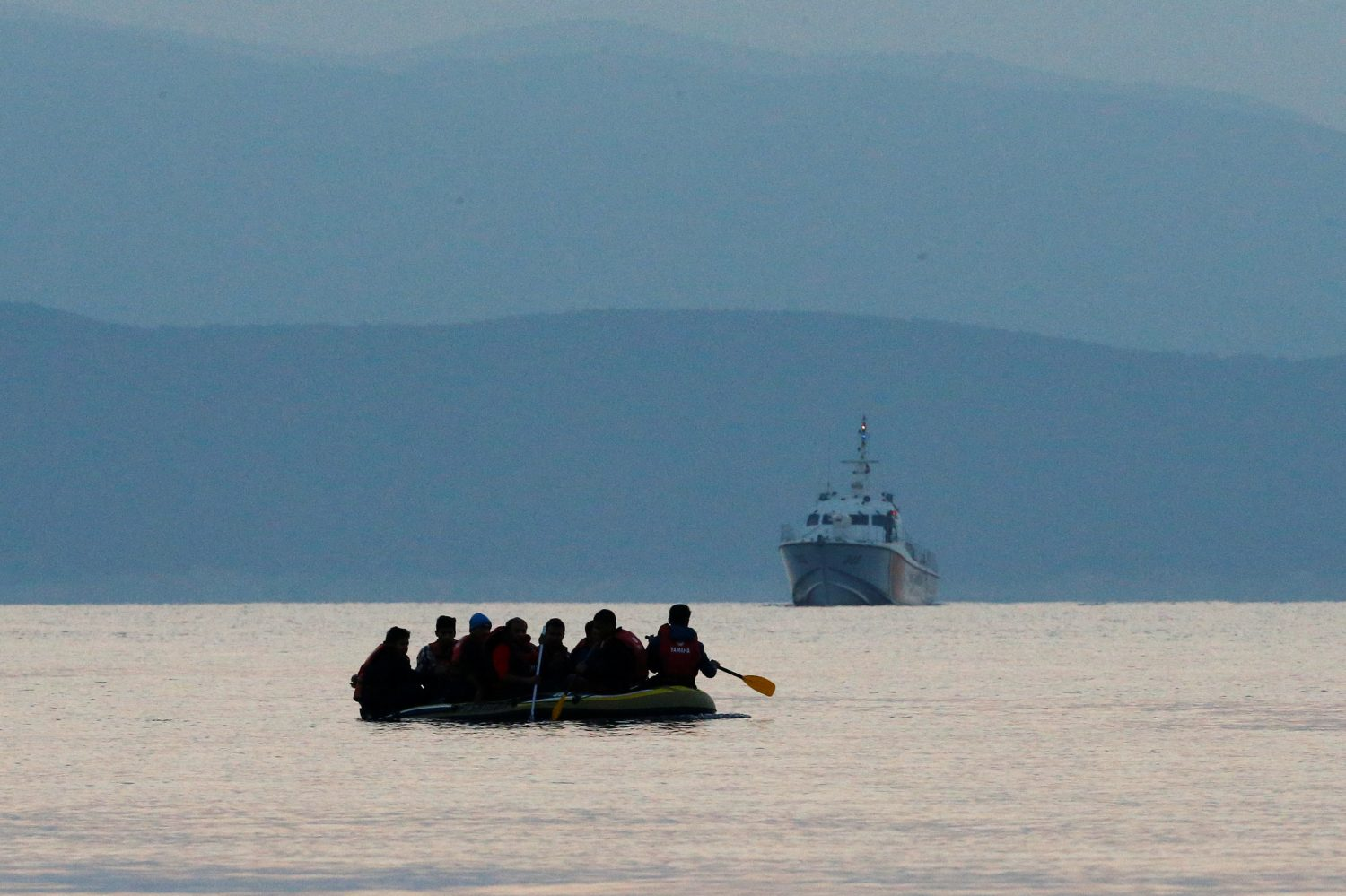 FILE PHOTO: Migrants in a dinghy paddle their way on the Mediterranean Sea to attempt crossing to the Greek island of Kos, as a Turkish Coast Guard ship patrols off the shores off Bodrum, Turkey, September 19, 2015. REUTERS/Umit Bektas/File Photo