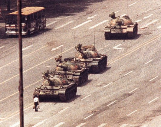 FILE PHOTO: A man stands in front of a convoy of tanks in the Avenue of Eternal Peace in Beijing, China, June 5, 1989. REUTERS/Arthur Tsang/File Photo