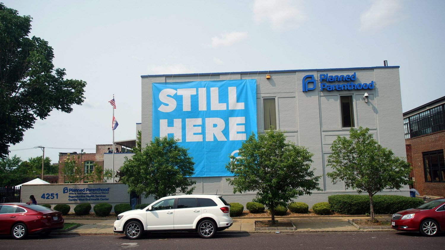 "A banner stating ""STILL HERE"" hangs on the side of the Planned Parenthood Building after a judge granted a temporary restraining order on the closing of Missouri's sole remaining Planned Parenthood clinic in St. Louis, Missouri, U.S. May 31, 2019. REUTERS/Lawrence Bryant"