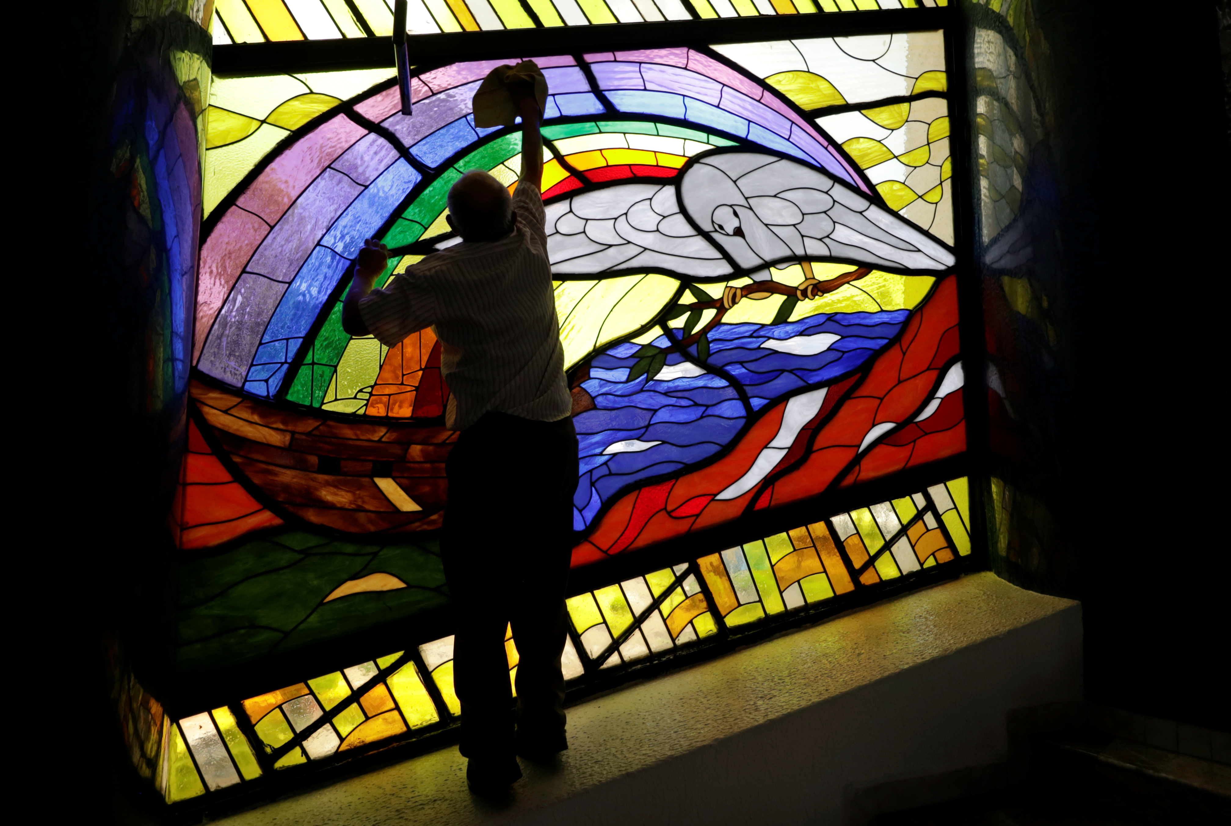A man cleans a stained glass inside a La Luz del Mundo (The Light of the World) church after its leader Naason Joaquin Garcia was arrested in California, in Mexico City, Mexico June 5, 2019. REUTERS/Luis Cortes