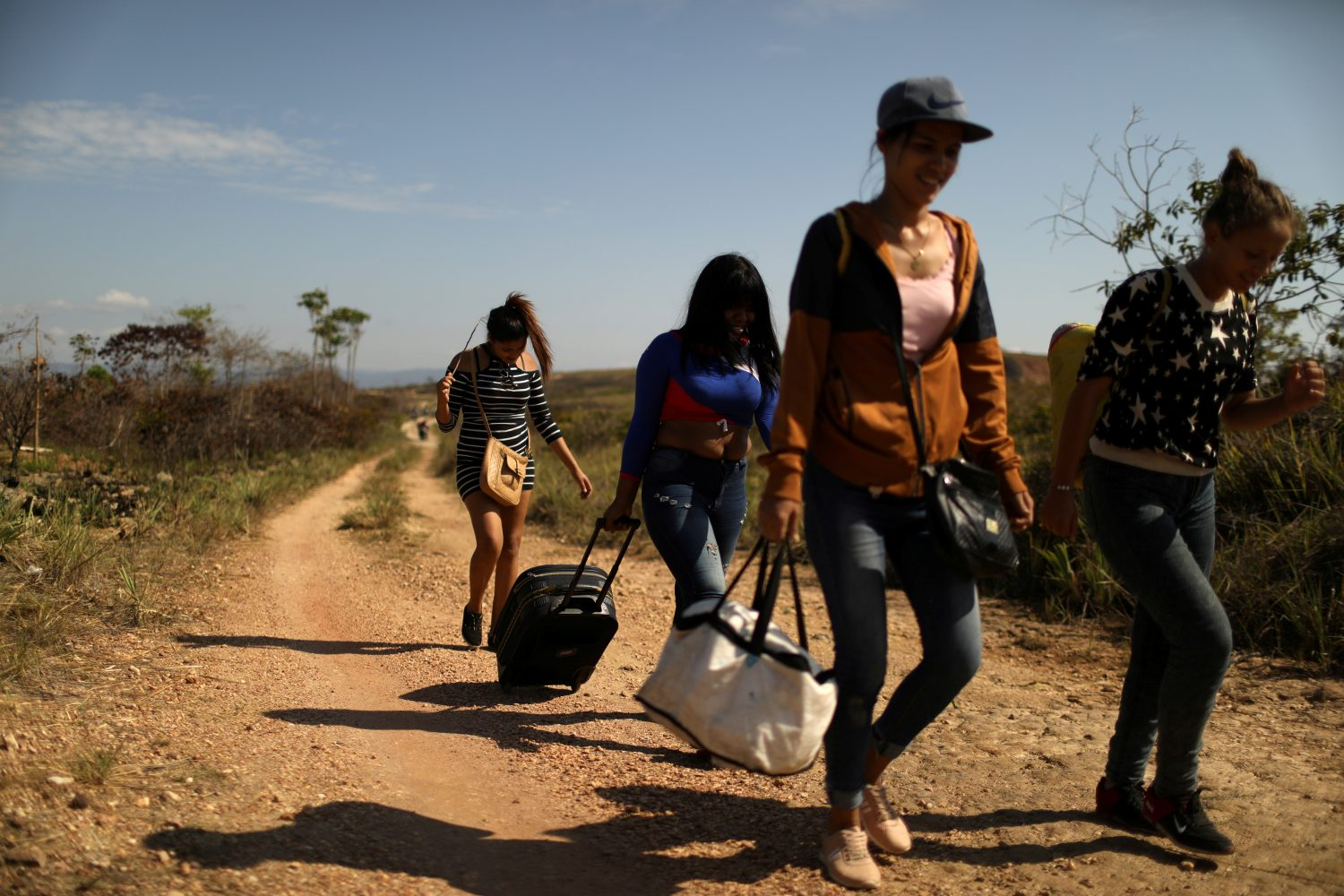 FILE PHOTO: Venezuelan migrants walk along a trail into Brazil, in the border city of Pacaraima, Brazil, April 11, 2019. REUTERS/Pilar Olivares/File Photo
