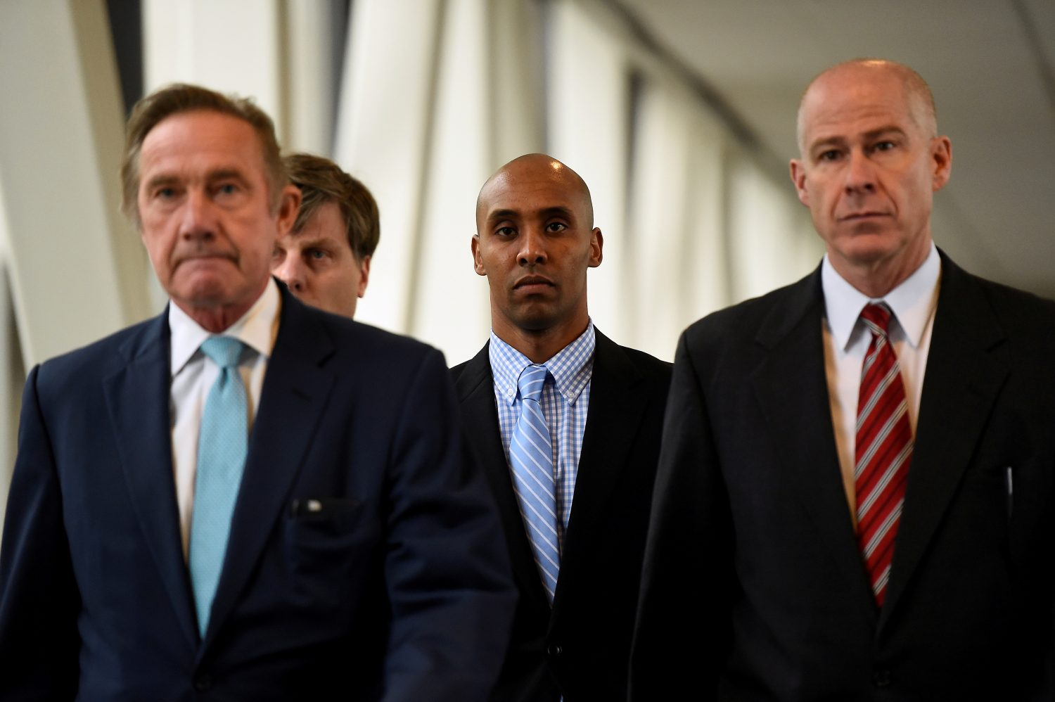 FILE PHOTO: Mohamed Noor, center, former Minnesota policeman on trial for fatally shooting an Australian woman, walks into the courthouse in Minneapolis, Minnesota, U.S., April 30, 2019. REUTERS/Craig Lassig/File Photo - RC1DDA04DCD0