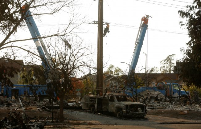 FILE PHOTO: A lineman from Pacific Gas & Electric (PG&E) works on a power line near a neighborhood destroyed by wildfire in Santa Rosa, California, U.S., October 12, 2017. REUTERS/Jim Urquhart