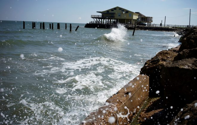 FILE PHOTO: The rising waters of the Gulf of Mexico crash at the shoreline of the Treasure Island community of West Galveston Island, Texas March 6, 2014. REUTERS/Rick Wilking/File Photo