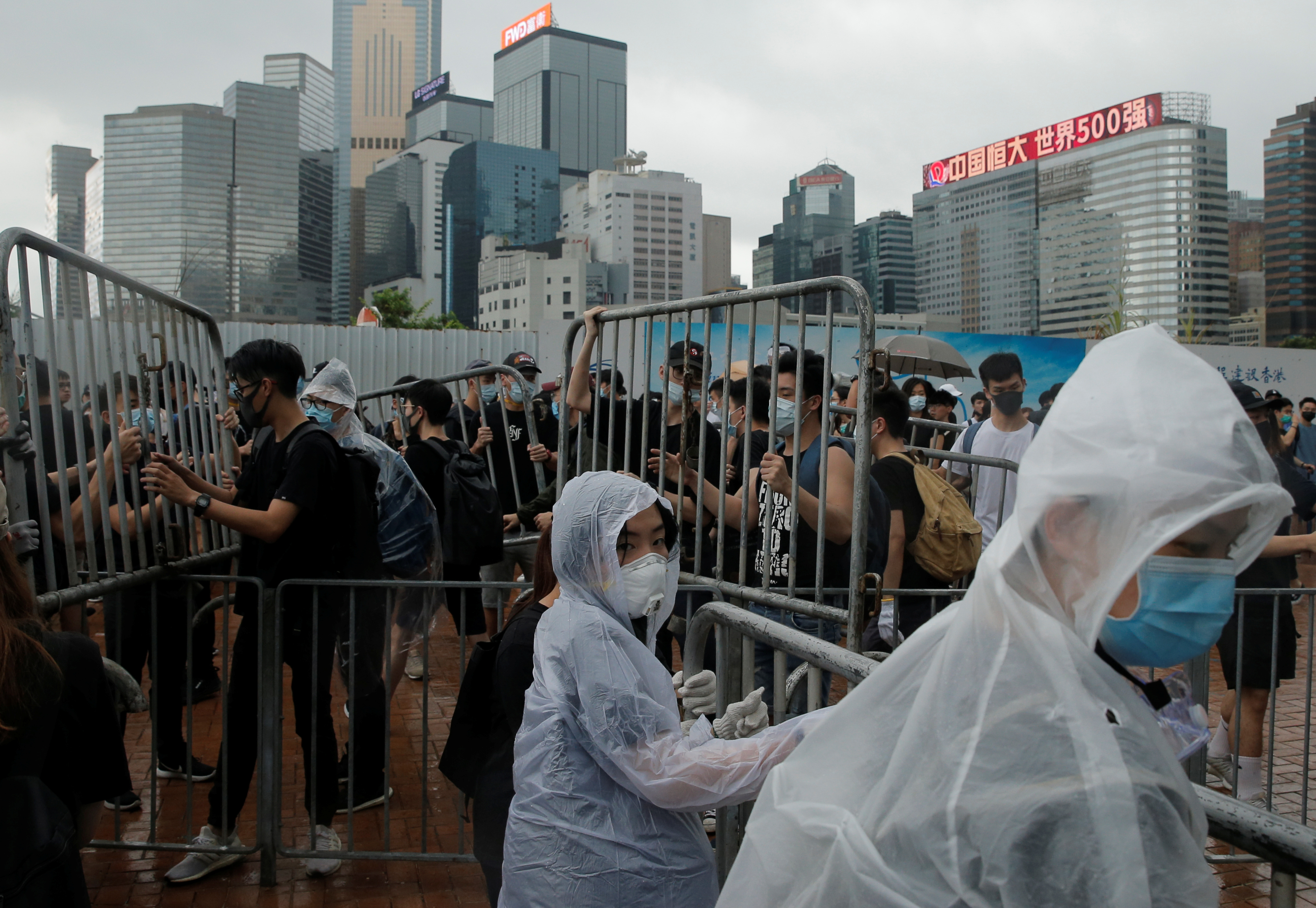 Demonstrators remove metal barricades during protests against a proposed extradition bill in Hong Kong, China June 12, 2019. REUTERS/Thomas Peter