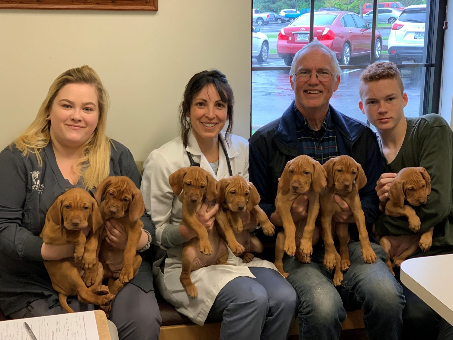 Destiny Brown, Dr. Katie Buss, and Kingsley family pose with puppies at the Kings Veterinary Hospital in Loveland, Ohio, U.S., on April 26, 2019. Picture taken on April 26, 2019. Courtesy Jennifer Blodgett/Kings Veterinary Hospital/Handout via REUTERS